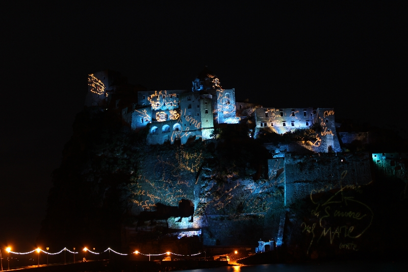 Castello Aragonese with blue lights and golden scriptures